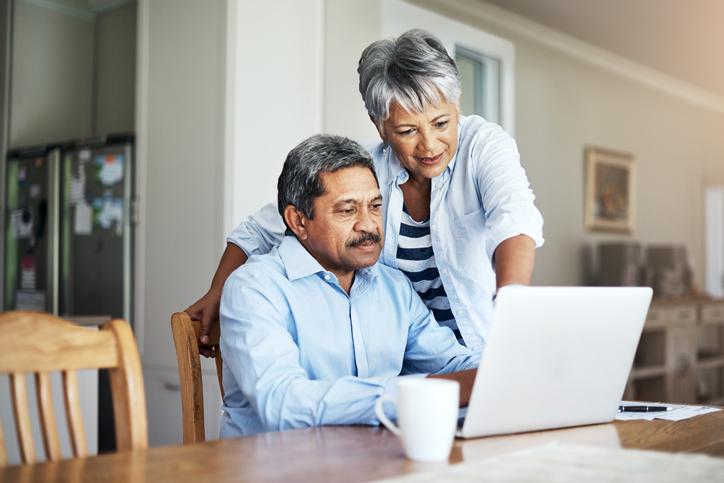 Happy couple working on laptop